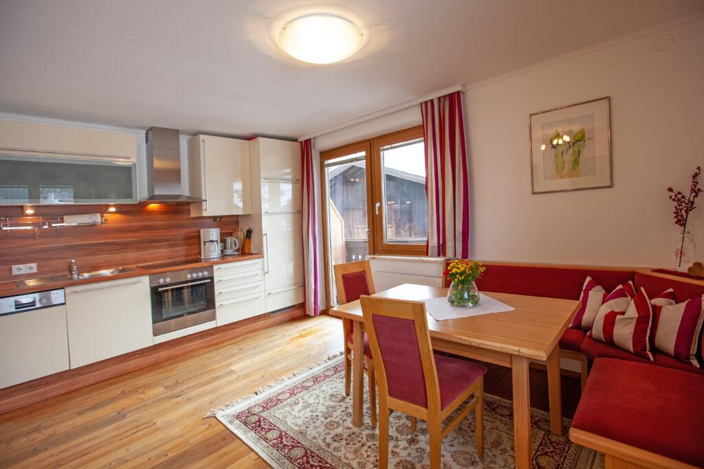 Blick zum Essbereich, Küchenzeile und Balkontüre im Apartment Lackenkogel