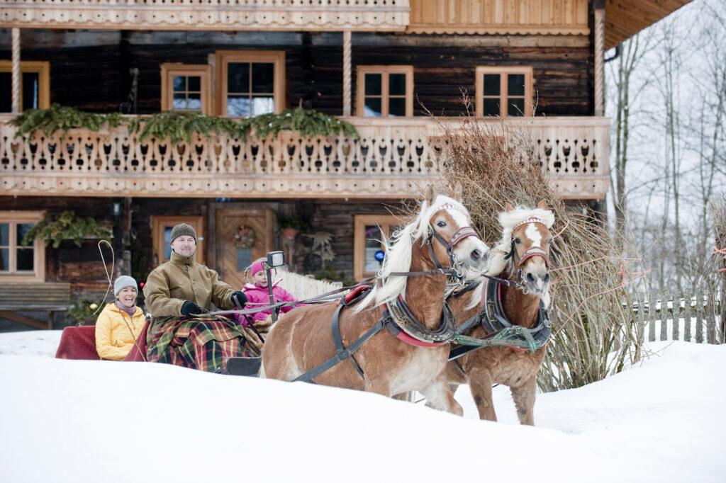Familie auf Pferdeschlitten vor einem alten Bauernhaus